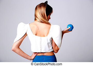 Back view portrait of a young woman with blue apple