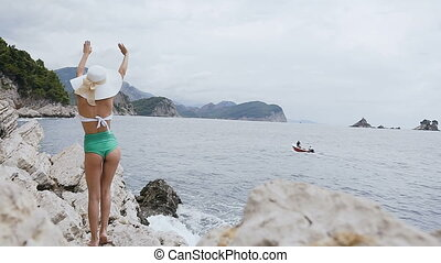 Back view. Slim tanned girl in a white-green swimsuit with big hat standing on a cliff raising her arms up accompanying two people who float on the boat by the sea. Vacation on Adriatic sea. Petrovac, Montenegro