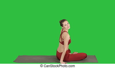 Sporty woman practicing yoga lotus pose, turning to camera...
