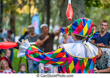 Back view streert juggler in bright clothing - Back view of...