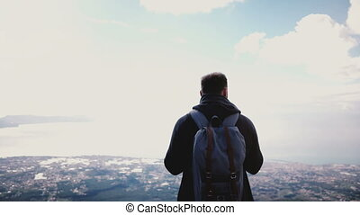 Back view successful happy tourist man enjoying amazing sky scenery view from the top of Vesuvius volcano, walking away. Excited male traveler enjoying incredible moments of life at epic locations.