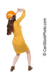 back view. woman in a dress and protective construction helmet protects hands from what is falling from above.