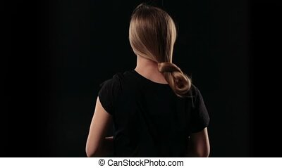 Back view woman letting down blond straight hair