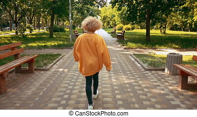 blonde female walks in city park in casual student in white sneakers and yellow sweater summer landscape slow motion