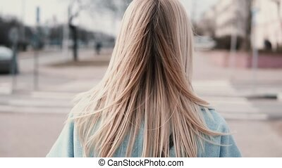 Back view woman with long blonde hair walking. Businesswoman...