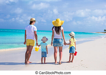 Back view young family of four on tropical beach