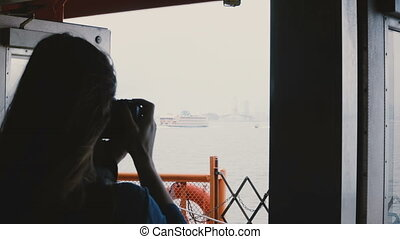 Back view young female traveler on board of a tour boat to Statue of Liberty taking photos with a camera on cloudy day.