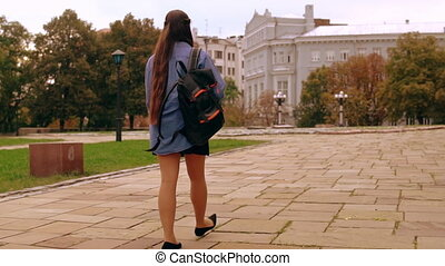 back view young woman walking with backpack in city -...