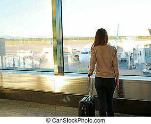 Back view young woman with suitcase in modern airport terminal
