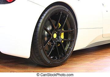 Back wheel and yellow caliper brakes of a bright white super car