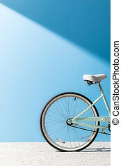 back wheel of bicycle in front of blue wall
