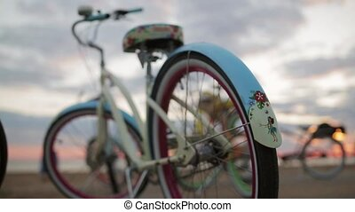 Back wheels of two bright bicycle focus in, among other in summer on beach