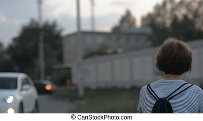 Back woman rides a bicycle in the evening