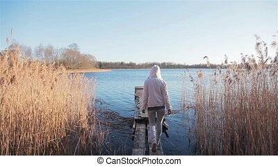 Back woman walk wooden pier sunny