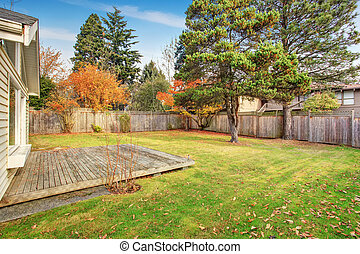 Large back yard with deck, trees, and grass.