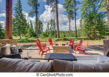 Back yard with fire pit and red chairs near newly bild luxury real estate home with forest biew and green grass.