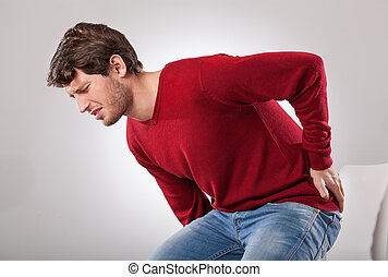Man with strong backache can't sit on the chair