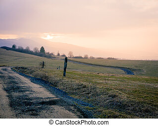 Backcountry dirt road, gravel path on foothills of lower tatras mountain in Slovakia at sunset time.
