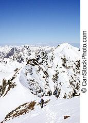 backcountry skier hikes along narrow mountain ridge in the Swiss Alps