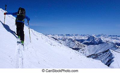 backcountry skier hikes up a mountain side in winter in the Swiss Alps