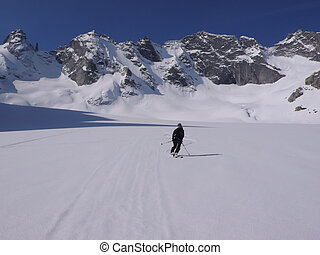 backcountry skier skiing on a picturesque glacier in the Alps of Switzerland with a great mountain landscape behind