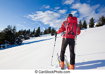 Backcountry skier - Young male backcountry skier moving up...