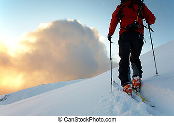 Backcountry skier walks in the snow at sunset, italian alps...