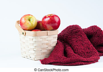 backet of red apples and a warm wool blanket on a white...