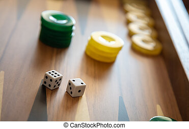 Backgammon, dice and chips closeup on game board.