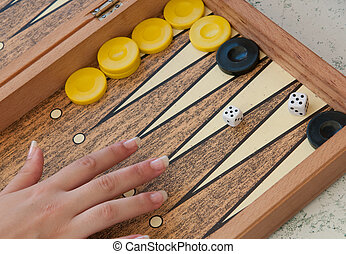 Backgammon game with hand throwing the dice.