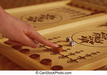 Backgammon game - Female hand moves a backgammon chip