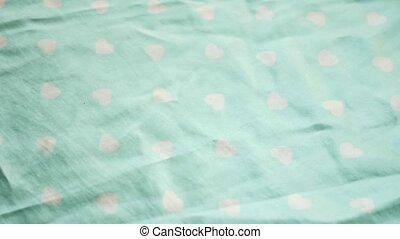 Background from bright satin fabric. closeup texture of crumpled fabric with a pattern of white hearts on a mint background