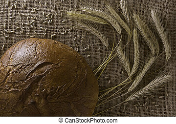 Background from burlap with rye bread and ears of a rye. Top view.