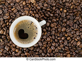 Background from coffee grains and a cup from coffee, the top...