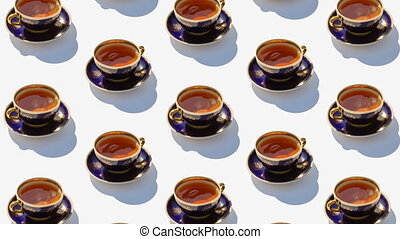 Background from large group of cups with tea. Stop motion animation. Ceramic cups revolve around their axes.  Flat lay, top view. Diagonal isometric view. Seamless loop video.