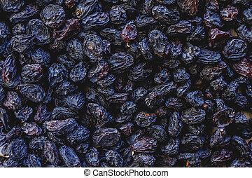 Background from dark blue raisins. Close-up.