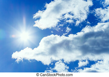 the blue sky with white clouds and the sun