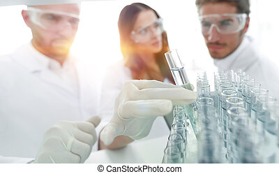 background image is a group of scientists studying the liquid in