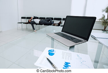 background image of a laptop on a glass table in an empty office