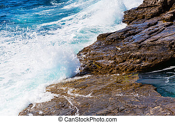 Background image of foam and waves on stone beach shore