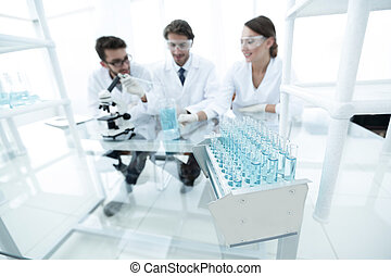 background image of scientists studying blue liquid in a flask