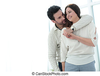 background image of the embracing couple standing in a new apartment