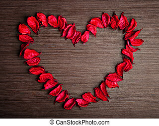 background in the style of Valentine's Day. petals of red roses in the shape of a heart on a wooden background