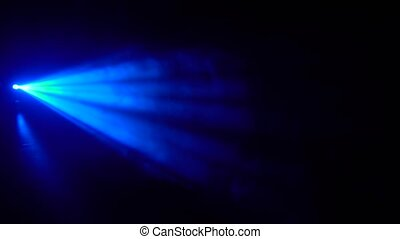 Background light performance. Blue rays on a black in smoke
