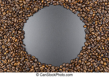 Background made of fresh roasted coffee beans lying flat on a black background with copy space in the shape of a circle.