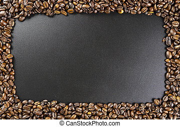 Background made of fresh roasted coffee beans lying flat on a black background with copy space in the shape of a rectangle.