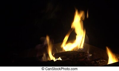 Background of a burning fire with a yellow flame in the dark. 4k