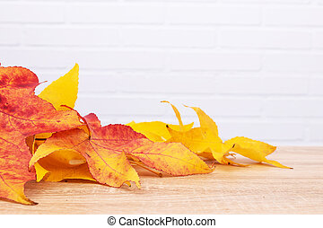 background of autumn leaves on wood with white brick
