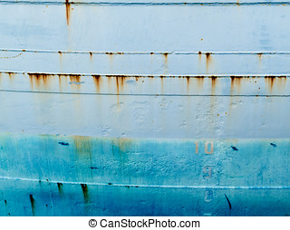 Background texture pattern of blue painted grungy steel hull of ocean ship close-up