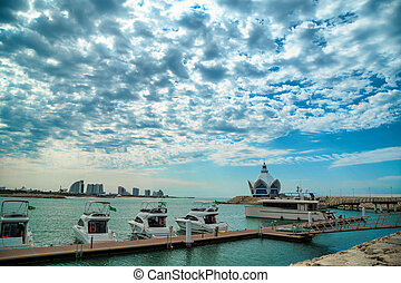 background of blue sky with beautiful clouds and azure sea with Marina and yachts. the focus is selective.